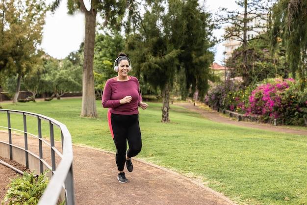 Mulher curvilínea fazendo corrida de rotina ao ar livre no parque da cidade - foco no rosto