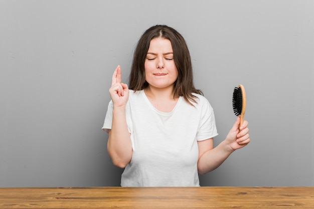Mulher curvilínea jovem e gorda segurando uma escova de cabelo cruzando os dedos para ter sorte