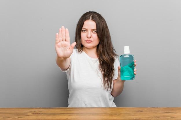 Mulher curvilínea jovem plus size segurando um anti-séptico bucal em pé com a mão estendida, mostrando o sinal de pare, impedindo você.