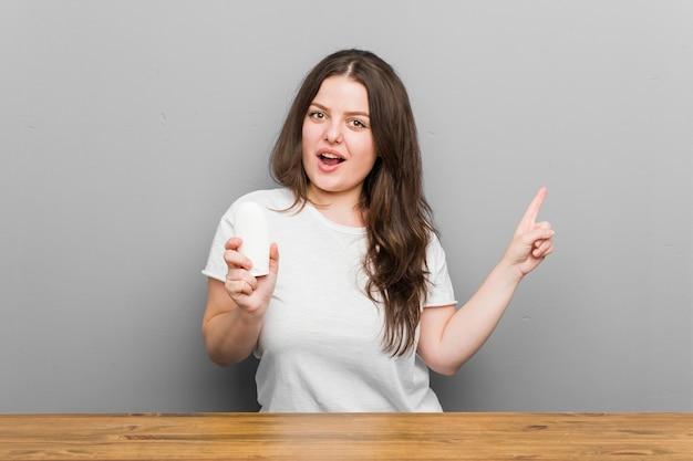 Mulher curvilínea jovem plus size segurando um hidratante sorrindo alegremente, apontando com o dedo indicador para longe.