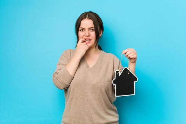 Mulher curvilínea jovem plus size segurando um ícone de casa roendo as unhas, nervosa e muito ansiosa.