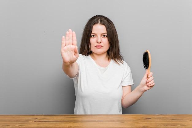 Mulher curvilínea jovem plus size segurando uma escova de cabelo em pé com a mão estendida, mostrando o sinal de pare, impedindo você.