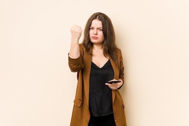 Mulher curvilínea nova que prende um telefone que mostra o punho à câmera, expressão facial agressiva.