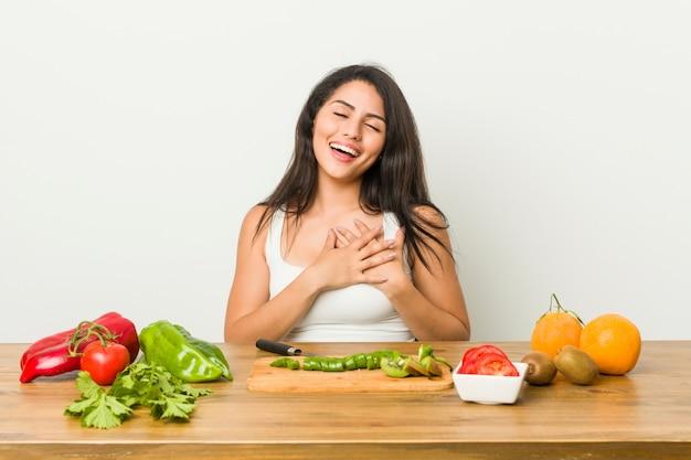 Mulher curvilínea nova que prepara uma refeição saudável que ri mantendo as mãos no coração, da felicidade.