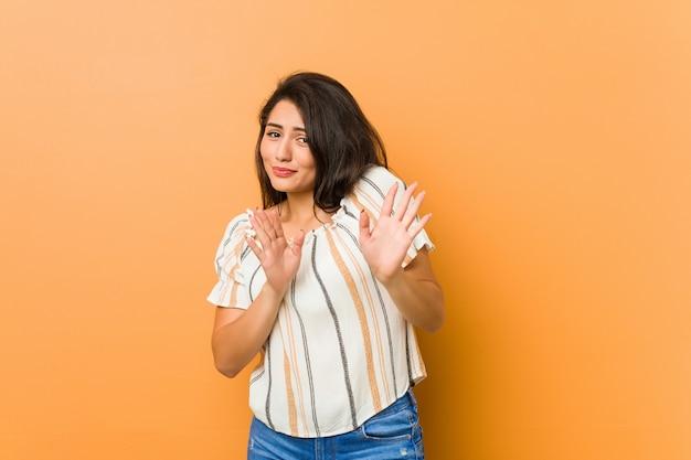 Mulher curvilínea nova que rejeita alguém que mostra um gesto de nojo.