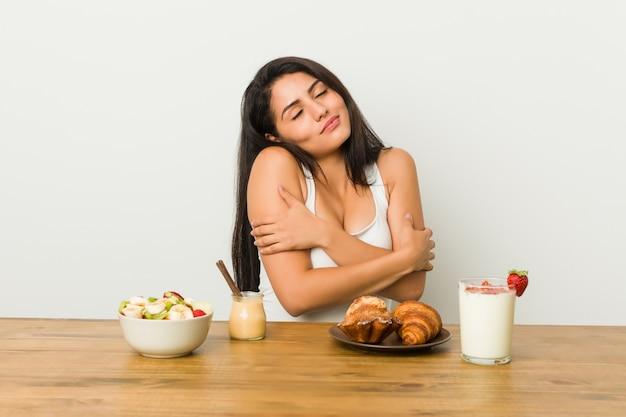 Mulher curvilínea nova que toma um abraço do café da manhã, sorrindo despreocupado e feliz.