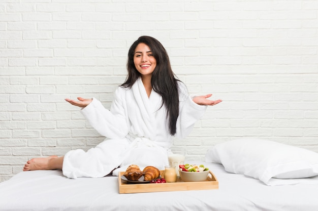 Mulher curvilínea nova que toma um café da manhã na cama que mostra uma expressão bem-vinda.