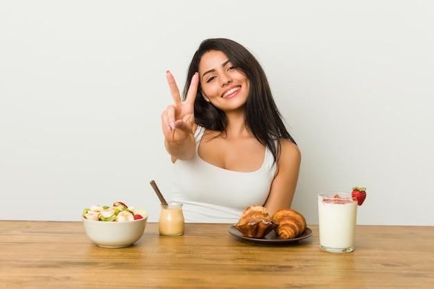 Mulher curvilínea nova que toma um café da manhã que mostra o número dois com dedos.