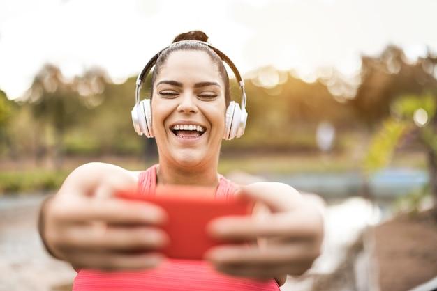 Mulher curvilínea tirando uma selfie com o celular enquanto pratica corrida de rotina ao ar livre no parque da cidade - foco no rosto