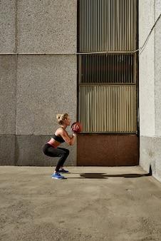 Mulher da aptidão que elabora no gym do ar livre usando a esfera de medicina.