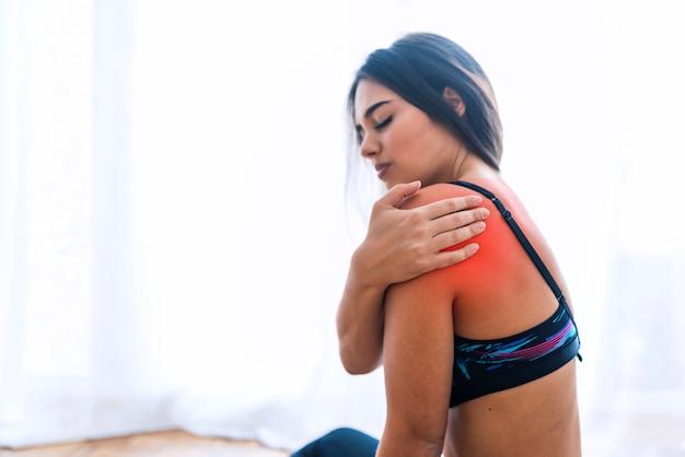 Mulher da aptidão que sofre da lesão no ombro durante o exercício. copie o fundo do espaço.