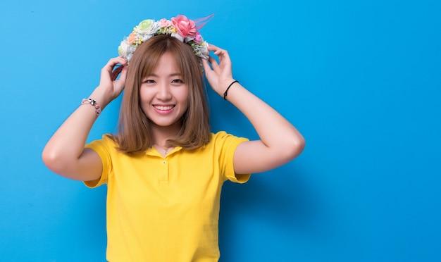 Mulher da beleza que levanta com o chapéu da flor na frente do fundo da parede azul