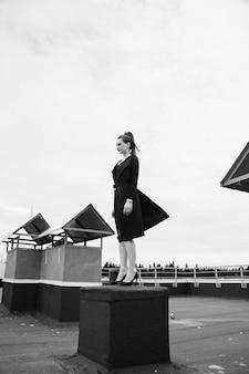 Mulher da cidade grande com rabo de cavalo de pé no topo do telhado em um vestido preto soprado pelo vento. preto e branco.