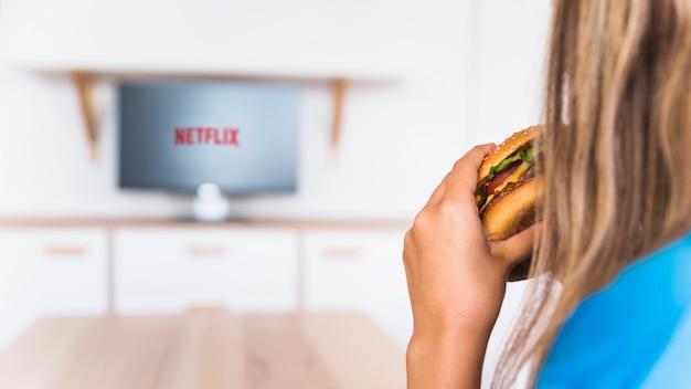 Mulher da colheita que come o hamburger e que presta atenção à série de televisão