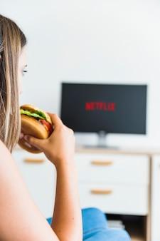 Mulher da colheita que come o hamburger e que presta atenção à série
