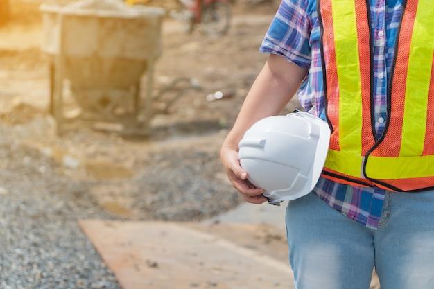 Mulher da engenharia que guarda um pé branco do capacete de segurança na frente do canteiro de obras.