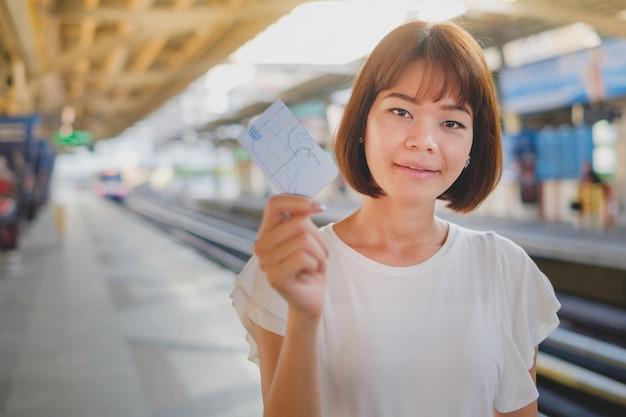 Mulher da felicidade que guarda o bilhete novo do smart card com fundo do borrão do trem de céu.