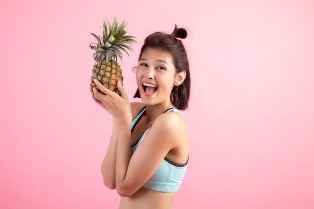 Mulher da fruta do abacaxi que sorri saudável e alegre após o exercício para controlar o peso