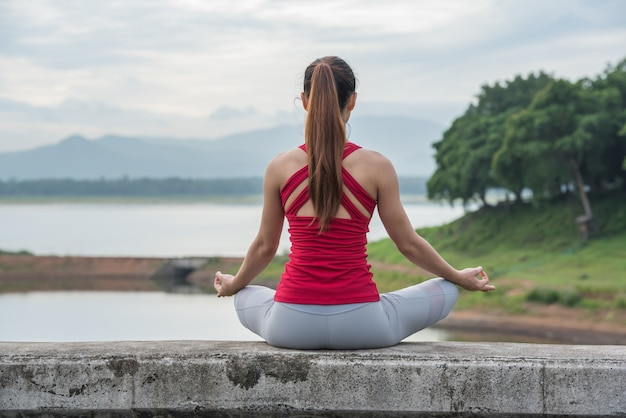 Mulher da ioga que faz a meditação no lago, vista traseira.