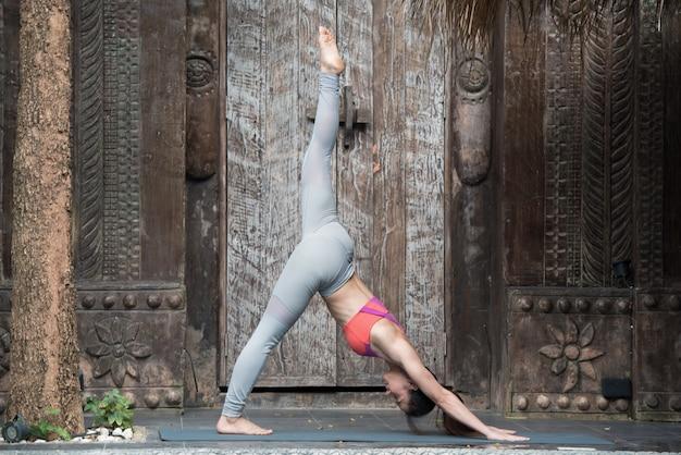 Mulher da ioga que faz o exercício com pose da ioga em casa.