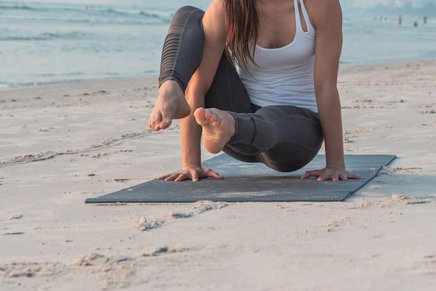 Mulher da ioga que faz o pose da ioga na praia, fim acima nos pés.