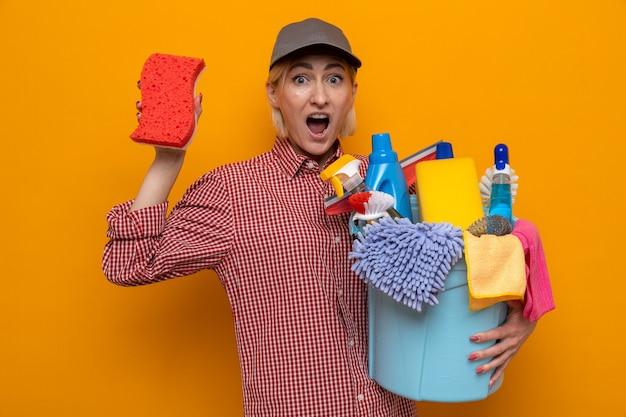 Mulher da limpeza com camisa xadrez e boné segurando a esponja e o balde com ferramentas de limpeza, olhando para a câmera espantada e surpresa em pé sobre um fundo laranja