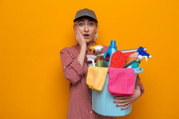 Mulher da limpeza com camisa xadrez e boné segurando um balde com ferramentas de limpeza, olhando para a câmera espantada e surpresa em pé sobre um fundo laranja