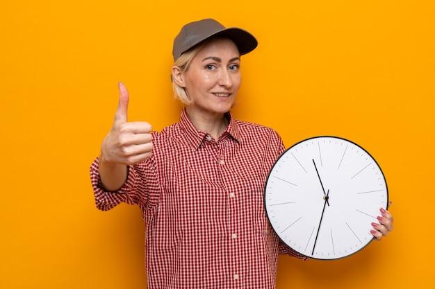 Mulher da limpeza com camisa xadrez e boné segurando um relógio, olhando sorrindo e mostrando os polegares para cima