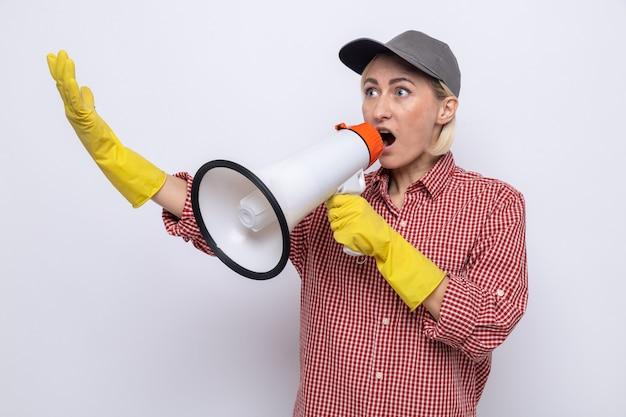 Mulher da limpeza com camisa xadrez e boné usando luvas de borracha gritando para o megafone e parecendo preocupada, fazendo gesto de parada com a mão em pé sobre fundo branco