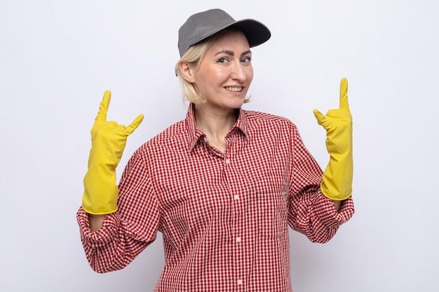 Mulher da limpeza com camisa xadrez e boné usando luvas de borracha, olhando para a câmera feliz e alegre, mostrando o símbolo do rock em pé sobre um fundo branco
