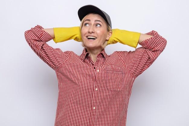Mulher da limpeza com camisa xadrez e boné usando luvas de borracha, olhando para cima sorrindo alegremente com as mãos na cabeça