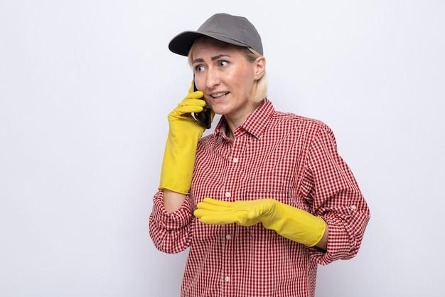 Mulher da limpeza com camisa xadrez e boné, usando luvas de borracha, parecendo confusa enquanto fala ao celular