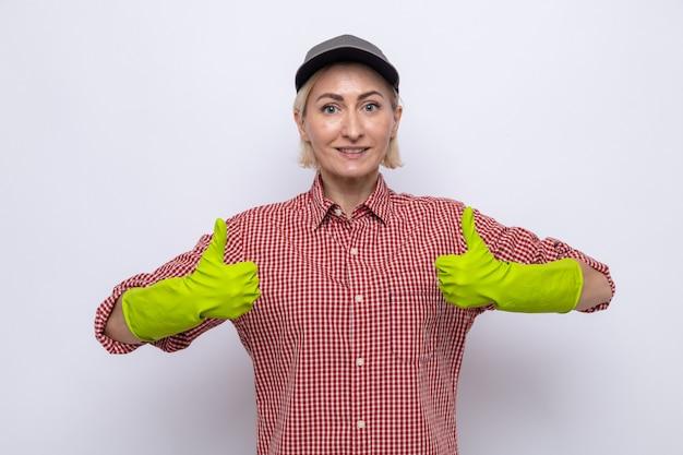 Mulher da limpeza com camisa xadrez e boné usando luvas de borracha, parecendo feliz e confiante sorrindo mostrando os polegares para cima
