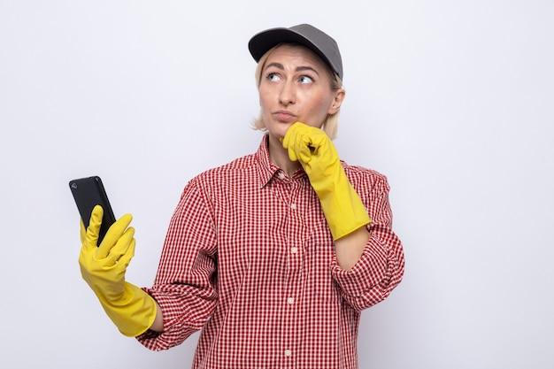 Mulher da limpeza com camisa xadrez e boné usando luvas de borracha segurando um smartphone, olhando para cima perplexa em pé sobre um fundo branco