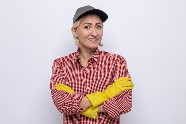 Mulher da limpeza com camisa xadrez e boné usando luvas de borracha, sorrindo no rosto com os braços cruzados