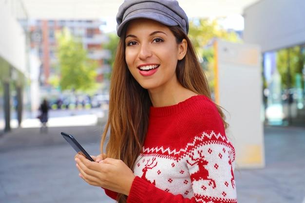 Mulher da moda de natal comprando online no telefone inteligente em shopping center.