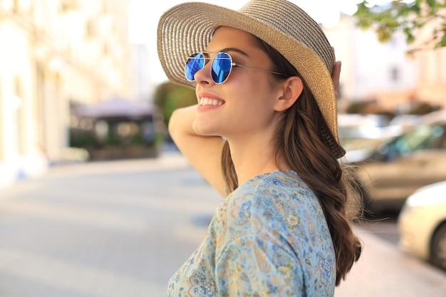 Mulher da moda do retrato está posando na cidade, moda de rua do verão. rindo e sorrindo retrato.