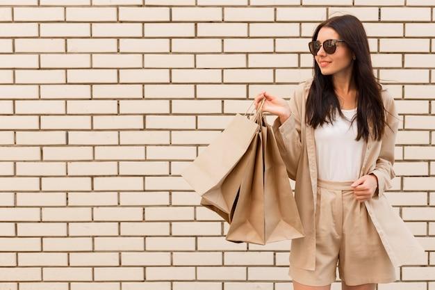 Mulher da moda segurando sacolas de compras cópia espaço parede de tijolos