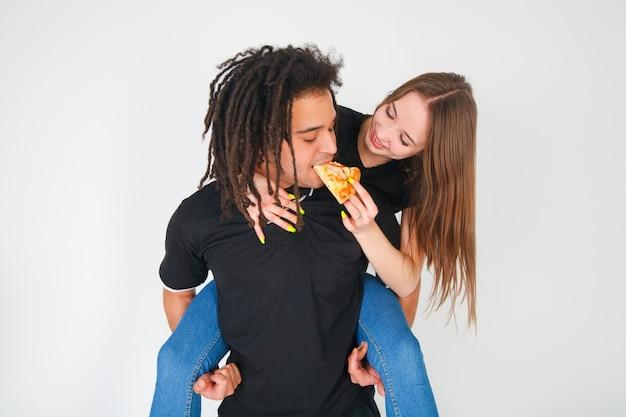 Mulher dá pizza para um cara, um jovem casal come pizza em um branco