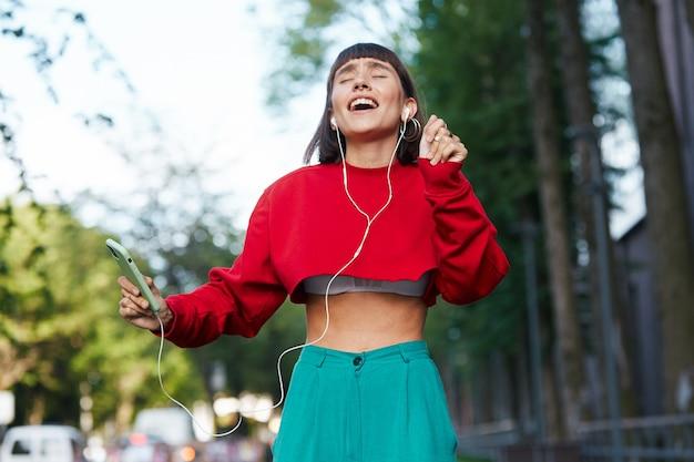 Mulher dançando e cantando na rua, linda mulher milenar em um suéter vermelho elegante canta e dança na rua com grandes emoções
