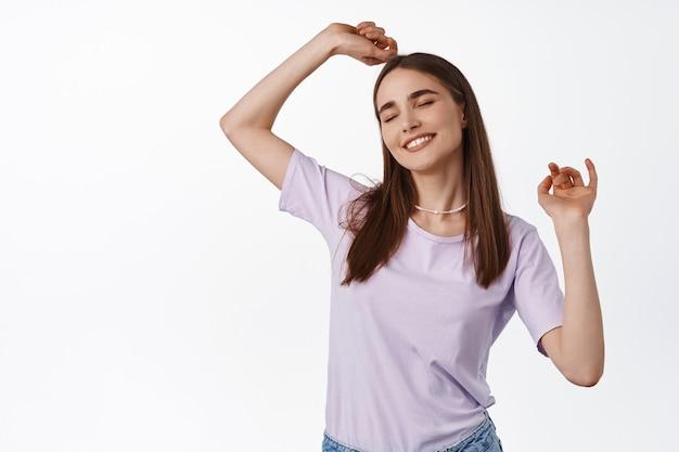 Mulher dançando e sorrindo, vestindo camiseta roxa em branco