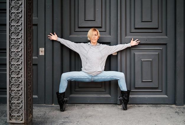 Mulher dançando na porta de um prédio com os pés na ponta dos pés e os braços cruzados. dança urbana