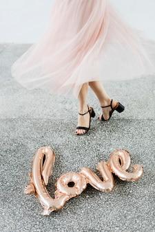 Mulher dançando perto do balão de alumínio no chão