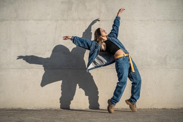 Mulher dançarina fazendo pose de águia vestido casual e sombra refletida na parede