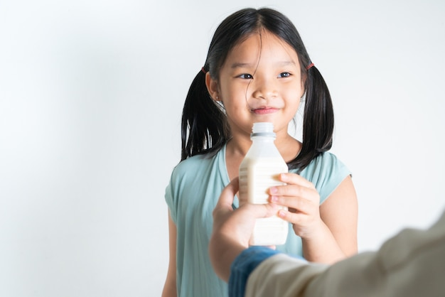 Mulher dando a filha uma garrafa de leite em casa