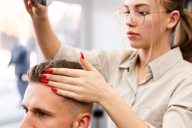 Mulher dando a um cliente um corte de cabelo no salão