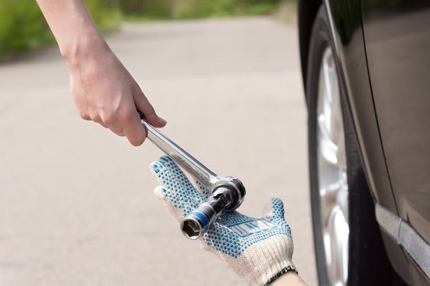 Mulher dando a um mecânico uma chave de boca ou chave inglesa enquanto ele trabalha