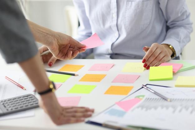 Mulher dando adesivo rosa para um colega na mesa do local de trabalho em metas e objetivos de escritório em