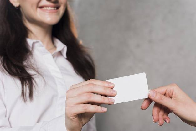 Mulher dando cartão de visita para potencial empregado