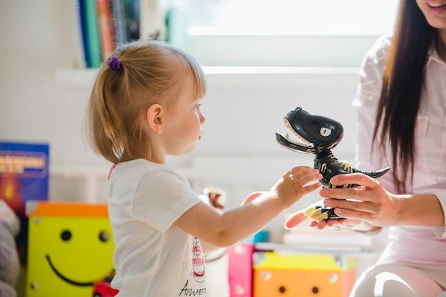 Mulher dando dinossauro para garota